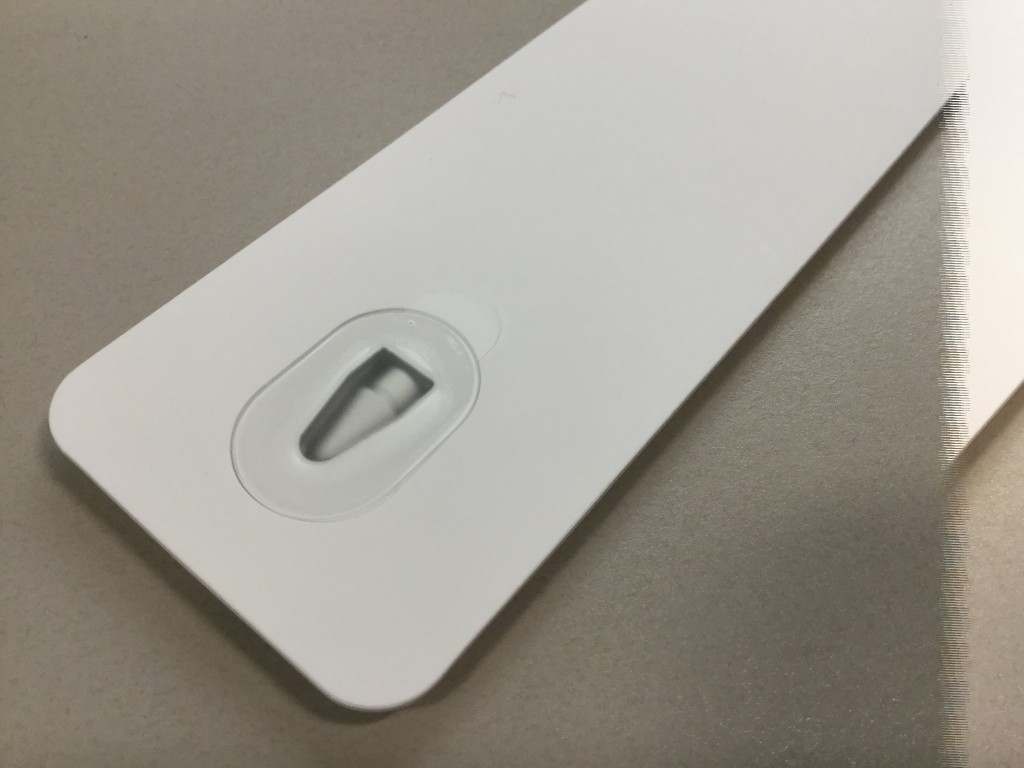 Flipping the package over reveals Apple included an access hole, covered in a small sticker with a tab to use to pull it off.